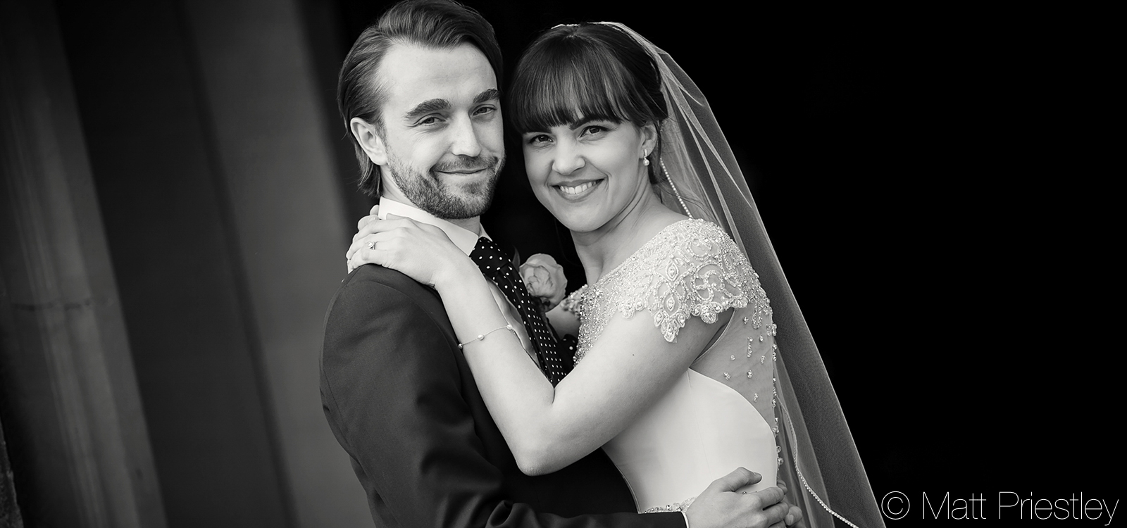 Couple-embracing-and-smiling-at-the-camera-in-the-doorway-or-Cheshire-Wedding-venue-Arley-Hall