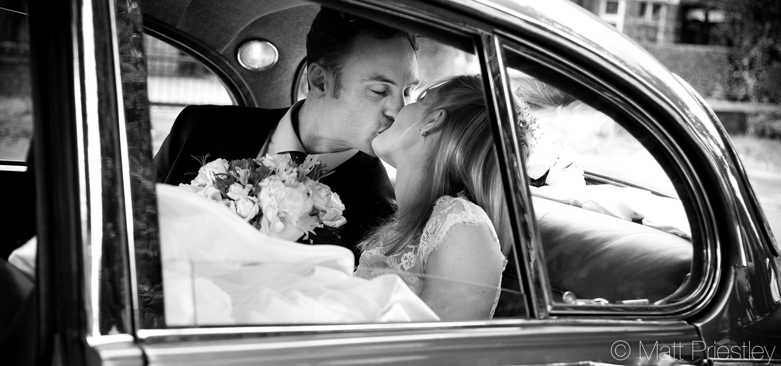 Newly-married-couple-kissing-in-the-back-of-a-vintage-car1